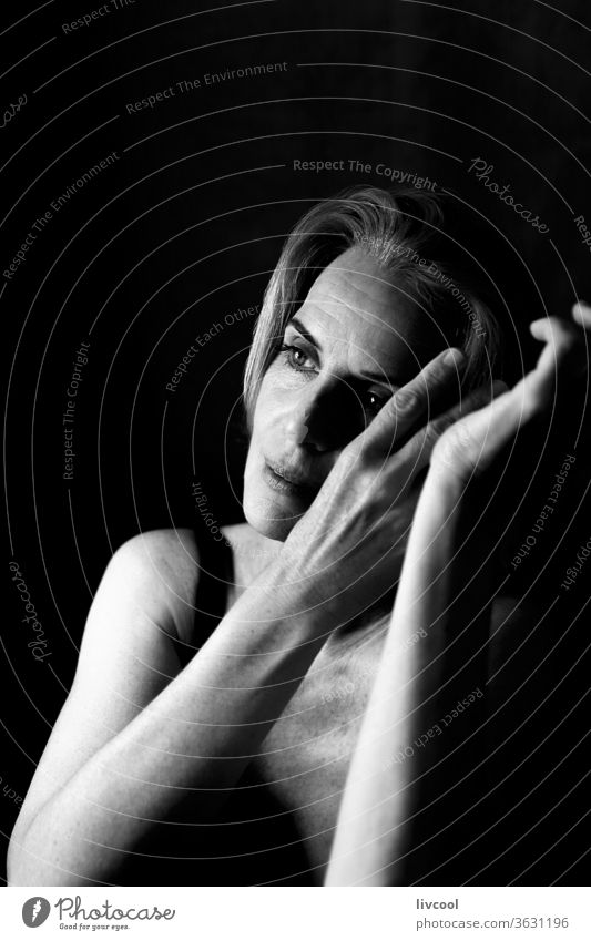 woman in a thoughtful and romantic attitude between light and shadow portrait people black and white one people asking silence gesture maturity adulthood