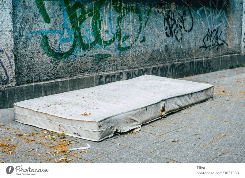 An old mattress on the street from graffiti. Concept of housing shortage and homelessness. House hunting Mattress Homelessness out Old Sleep Distress Poverty