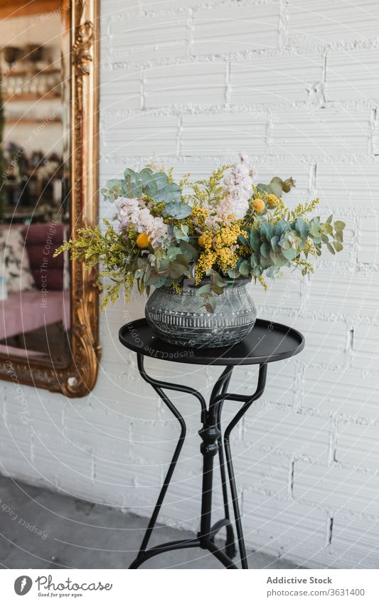 Ceramic vase with colorful flowers on table bouquet floristry fresh natural various pot creative beautiful eucalyptus goldenrod craspedia plant decor design