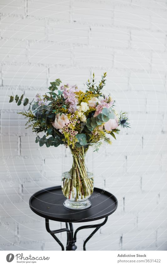 Glass vase with colorful flowers on table bouquet floristry fresh natural various glass pot creative beautiful craspedia plant decor design composition