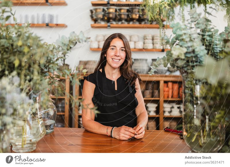 Positive owner of floristry workshop looking at camera woman floral happy success positive confident plant smile cheerful job small business professional