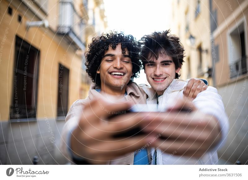 Cheerful gay couple taking selfie on smartphone homosexual hug together street lgbt mobile phone using multiracial diverse ethnic relationship cellphone photo