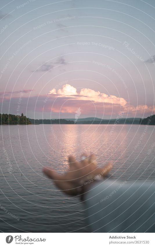 Anonymous person admiring sunset over lake travel nature traveler water evening hand harmony freedom landscape romantic enjoy journey tourism adventure