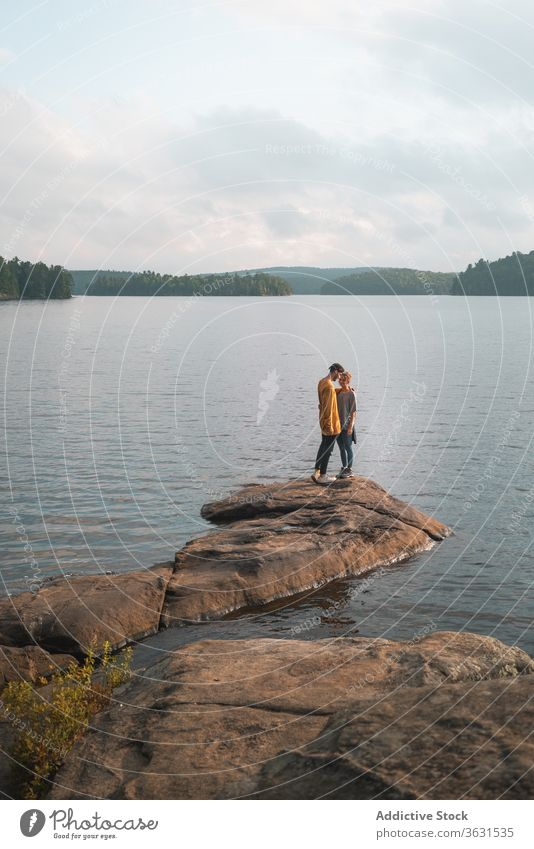 Couple kissing on stone near lake couple scenery tender algonquin provincial park picturesque romantic relationship travel canada together love affection nature