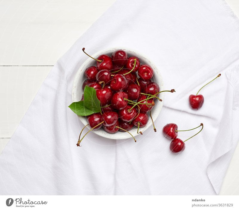 ripe red cherry in a round white wooden bowl on a white wooden background closeup crop delicious dessert agriculture berry bunch eating food fresh freshness