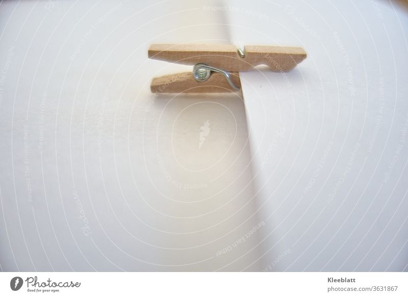 Single wooden clothespin clamped on a neutral white surface lateral view to the viewer Wooden clothespin, Remember, notice Text space in front, design,