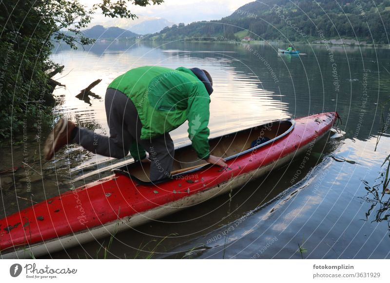 Man jumps into a canoe on a lake Boating trip boat go boating boat tour Boot camp Lakeside Watercraft Rowboat Vacation & Travel Trip Tourism Adventure Freedom