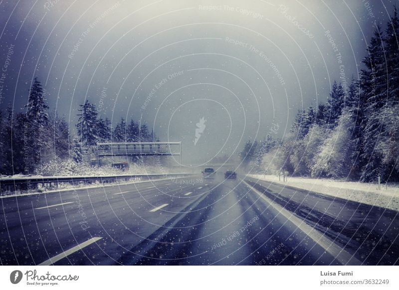 Germany, Bavaria, highway with rare traffic under snowstorm in winter car landscape white road forest wood fir tree vehicle lights season asphalt weather cold