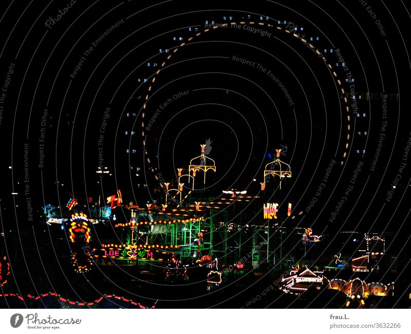 The hustle and bustle in Hamburg, the cathedral, sends colourful light into the night sky. Fairs & Carnivals Showman stalls Carousel Night Ferris wheel