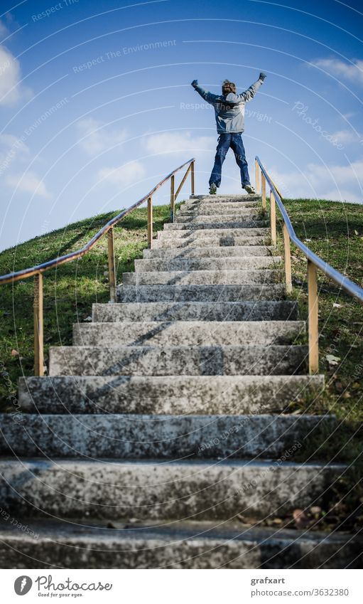 Boy On Top Of Outdoor Stairs On Hill Celebrates Success achieve achievement ambitious business career celebrate celebration challenge champion child climate