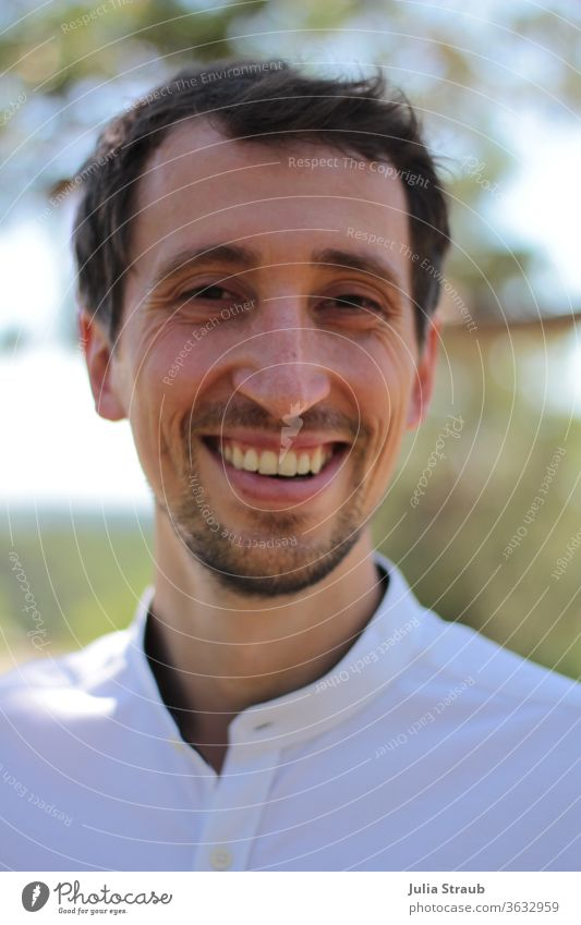 Young man in white shirt laughs Man Face of a man portrait Nature natural application motivated cheerful Facial hair Dark-haired Light (Natural Phenomenon)