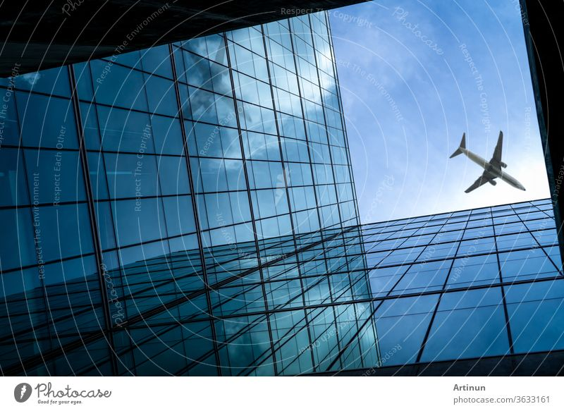 Airplane flying above modern glass office building. Perspective view of futuristic glass building. Exterior of office glass building. Business trip. Reflection in transparent glass. Company window.