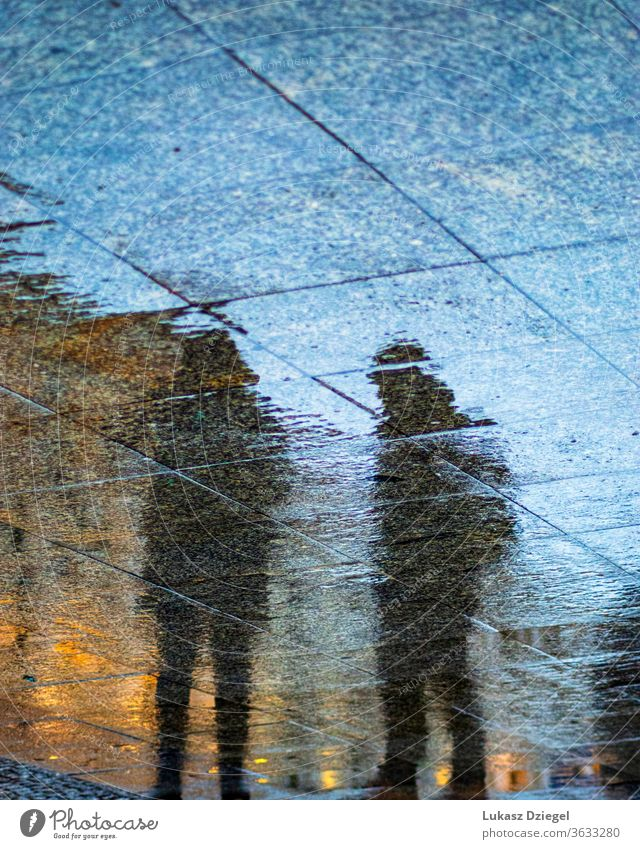 Silhouettes of people reflecting in the sidewalks wet from rain art shape creative blurry depressed surface ground mood life mirrored silhouette reflection