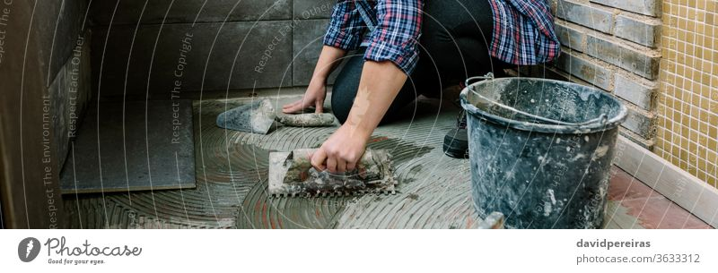 Female mason laying tiles on a terrace woman workman tiling floor imitation cement tile spread tiler glazed terrace working construction banner web panorama