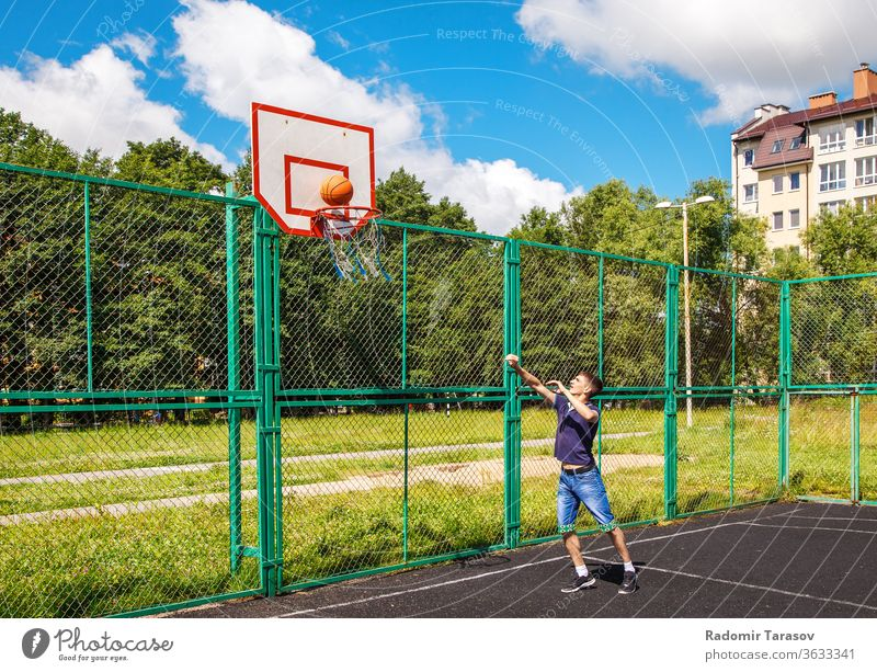young man playing basketball outdoor on bright sunny summer day street people urban city person adult lifestyle happy male outdoors leisure caucasian portrait