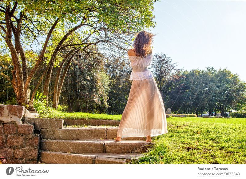 young girl in a light dress standing with her back in the park on sunny summer day woman one beauty nature lifestyle outdoor beautiful female person people