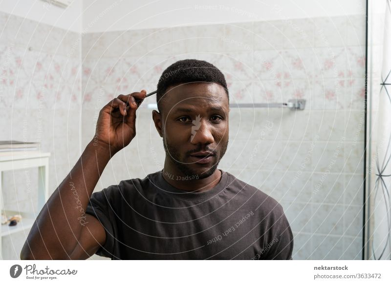 Young Black Man Combing Hair Looking at Camera combing hair face hairstyle man 1 person African ethnicity lifestyle 20-30 years old handsome domestic life