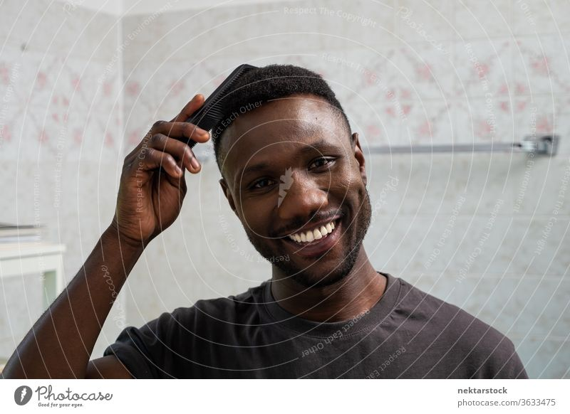 Handsome Black Man Smiling and Combing Hair in Bathroom combing hair face hairstyle man 1 person African ethnicity smile toothy smile smiling lifestyle