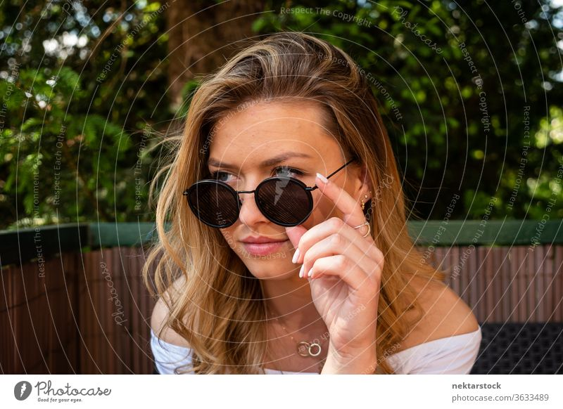 Pretty Blond Woman with Sunglasses Looking Away lifestyle blond young woman looking away vanity close up terrace summer one woman only caucasian ethnicity
