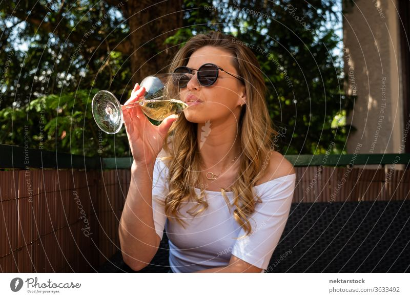 Young Woman with Sunglasses Drinking White Wine drinking lifestyle blond young woman sitting wine cup sipping white wine sparkling weekend sunglasses sunny