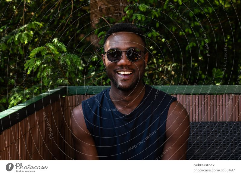 Young Black Man Smiling at Camera Outdoors 1 person African ethnicity man sunglasses lifestyle looking at camera terrace balcony summer tank top smile happiness
