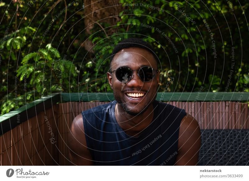 Young Black Man Towards Camera Outdoors 1 person African ethnicity man sunglasses lifestyle looking at camera terrace balcony summer tank top smile happiness