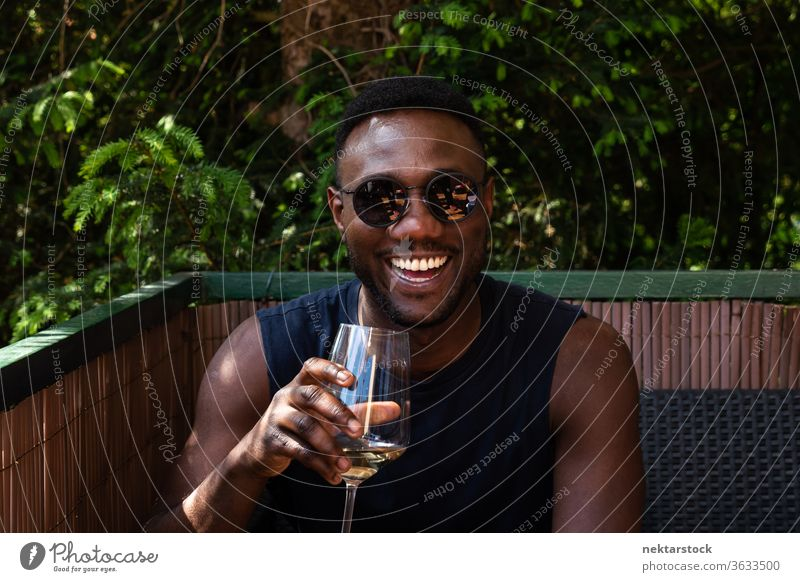 Handsome Black Man Holding Cup of Wine Smiling Widely Outdoors 1 person African ethnicity man sunglasses wine white wine cup holding lifestyle looking at camera
