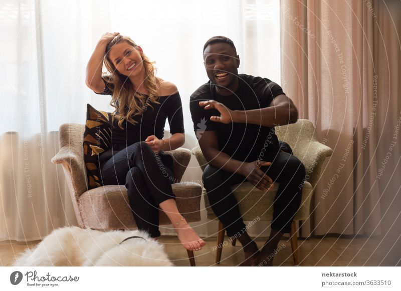Portrait of Mixed Race Couple Seated in Armchairs Smiling at Camera lifestyle couple 2 people smiling male female mixed race couple waving real life real people