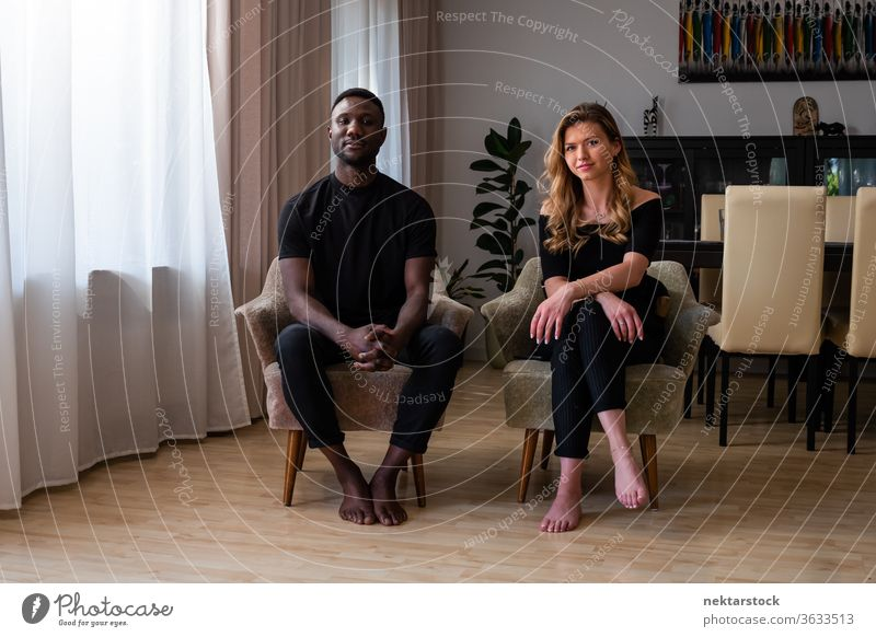 Portrait of Mixed Race Couple Seated in Living Room Armchairs lifestyle couple 2 people male female portrait mixed race couple real life real people full length