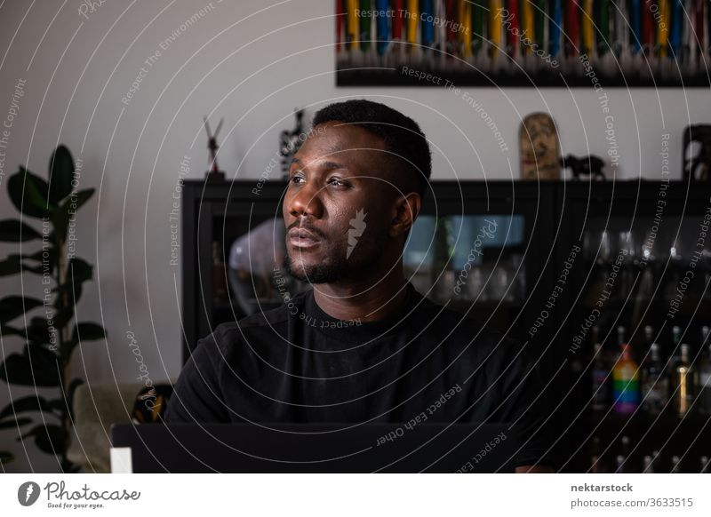 Portrait of Handsome Black Man Sitting in Living Room Looking Away man 1 person African ethnicity lifestyle 20-30 years old handsome domestic life young man