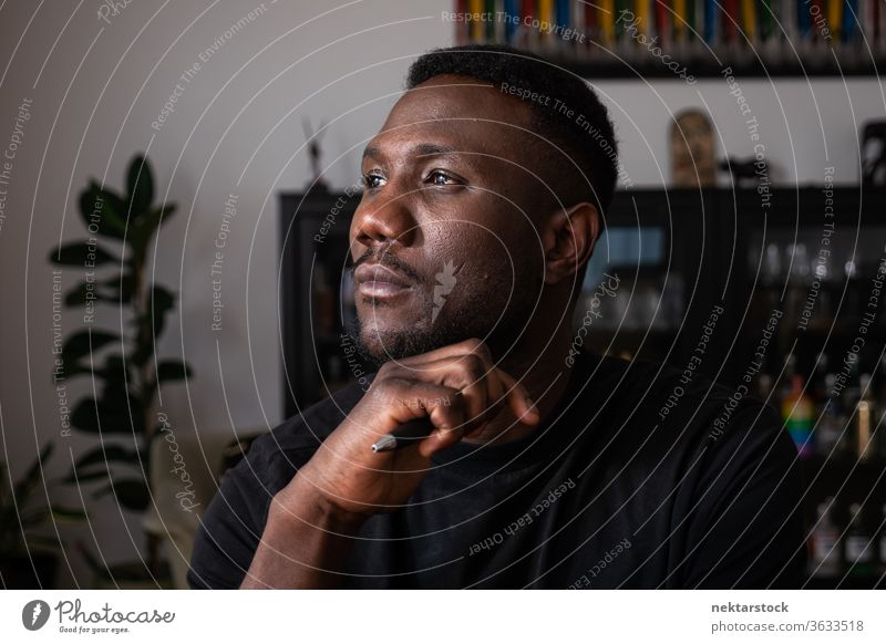 Portrait of Black Man Thinking in Living Room man 1 person hand on chin African ethnicity lifestyle 20-30 years old handsome domestic life young man male