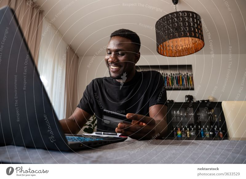 Young Black Man Smiling Online Shopping from Living Room credit card online shopping bank card man smiling happiness positive emotion purchase African ethnicity