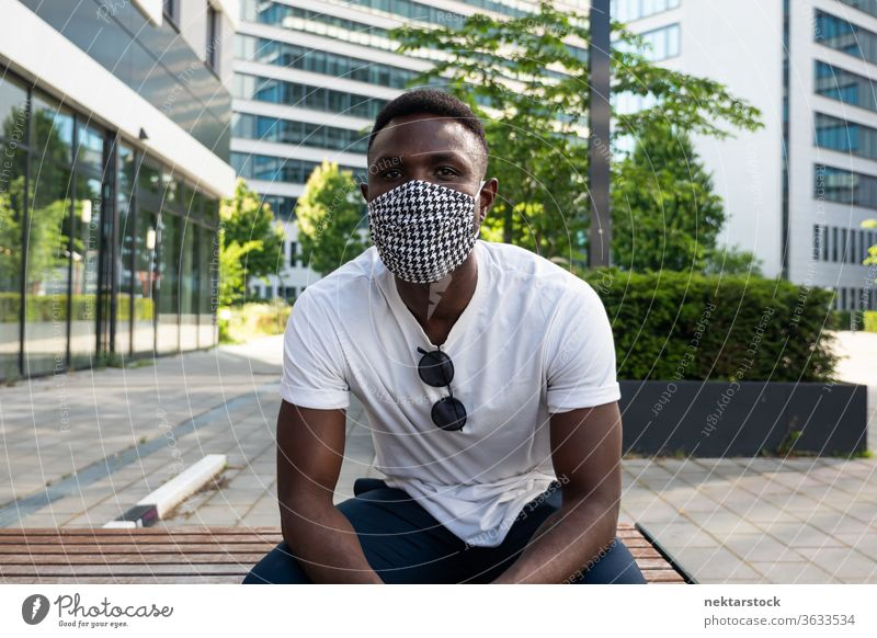 Young Black Man Wearing Face Mask Looking at Camera 1 person African ethnicity man lifestyle looking at camera bench summer medium shot portrait relaxation