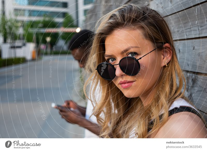 Young Woman with Round Sunglasses Looking at Camera woman portrait sunglasses blurred background smartphone lifestyle looking at camera 2 people male female
