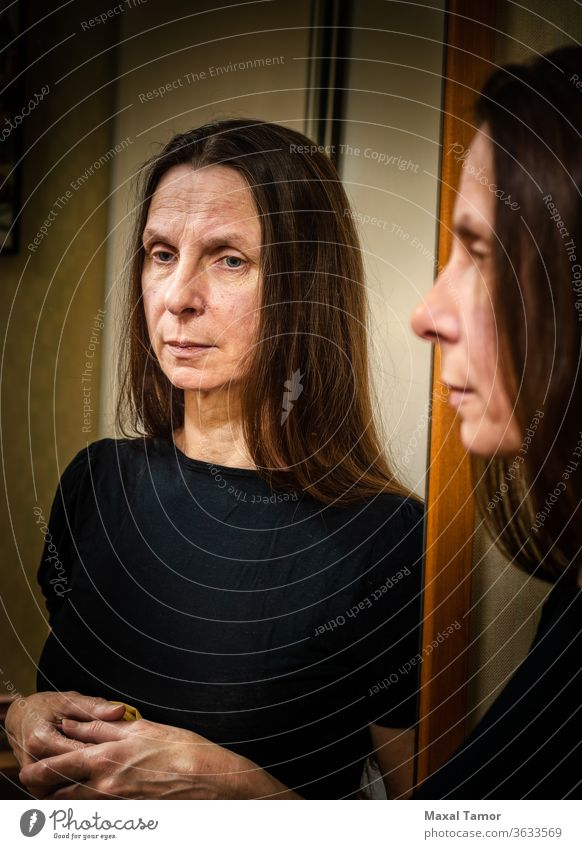 Portrait of an adult woman  reflecting in a mirror 60s Domestic Life aged attractive beautiful beauty brunette casual caucasian elderly expression face female