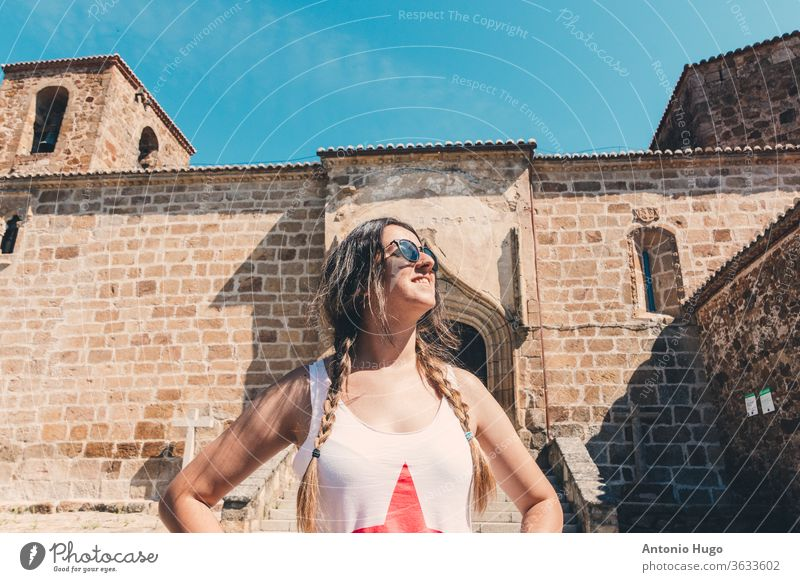 Blonde girl with braids in a rural village. Romanic chuch background. blonde female door aged closed entrance entry grunge latin photography poor scratches