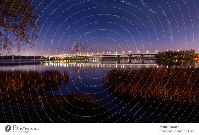 View of the Pivnichnyi Bridge on the Dnieper river in Kiev, Ukraine Dnieper River Kyiv Typha Latifolia autumn beauty blue blue hour bridge bright bulrush calm