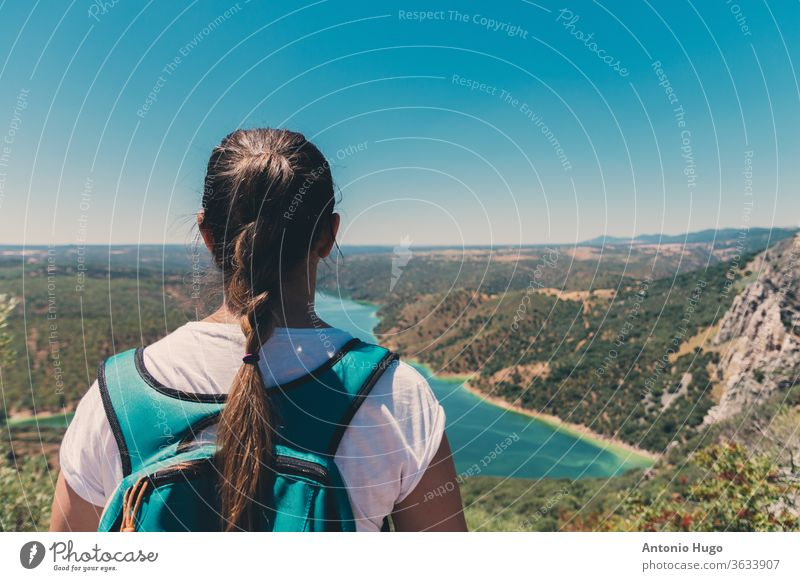 Blonde girl with braid looking at a beautiful mountain and lake landscape in Monfrague national park. blonde photography color image horizontal panorama scenery