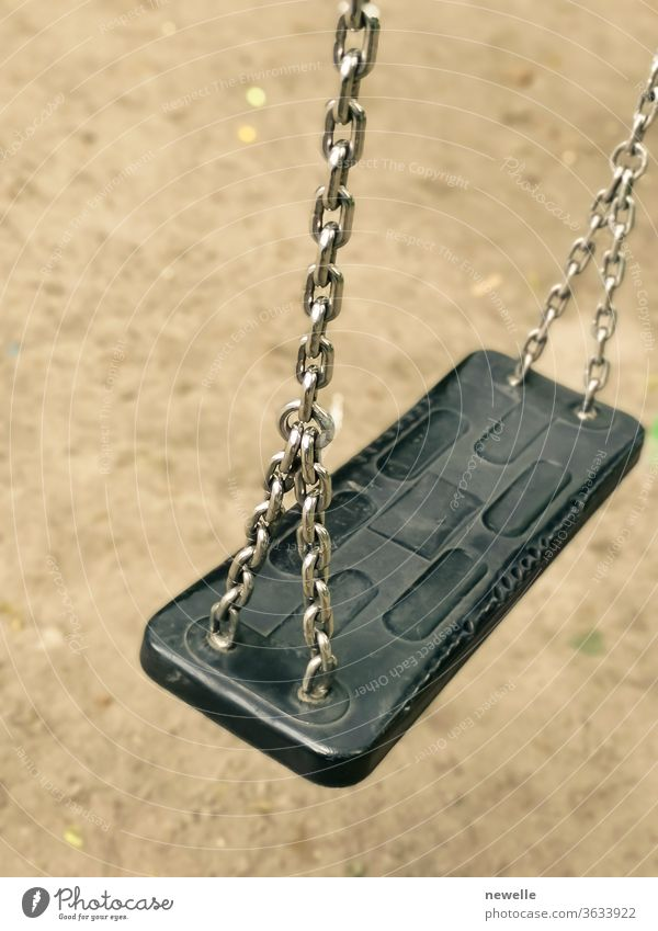 Empty swing on kids playground. vacant chain swing for children in a park on ground background. Close up photo. Corona virus causes empty playgrounds corona