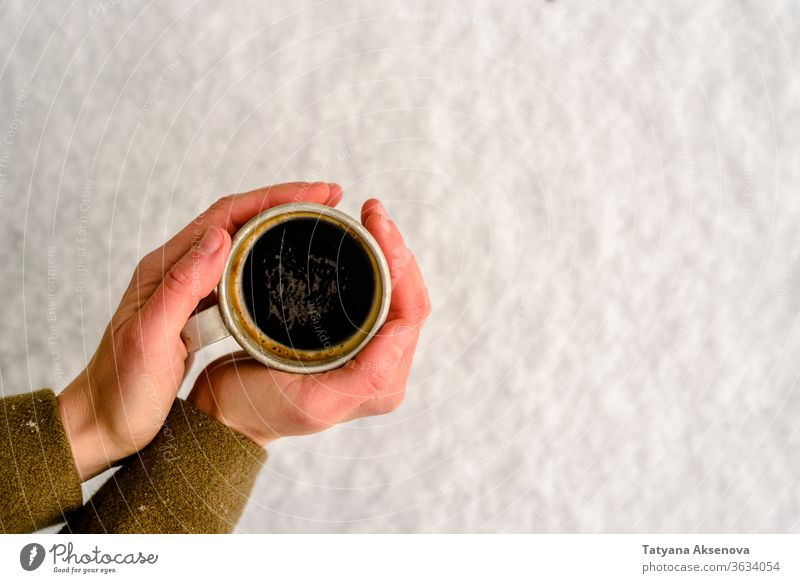 Old mug with hot coffee or tea drink on snow in winter cup cold mittens warm christmas holiday white beverage season xmas outdoor outside forest weather frozen