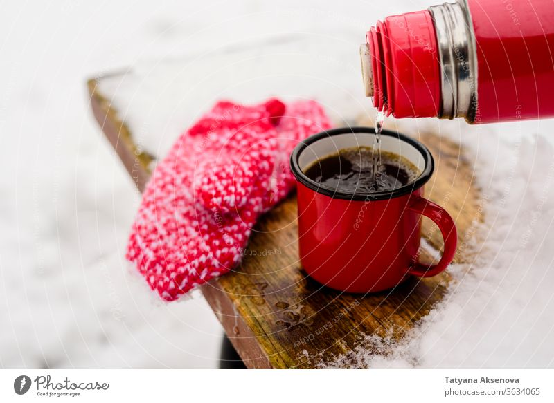 Red cup with hot coffee or tea drinking on snow in winter Hot Winter Mug Cup Snow Coffee Drinking chill mittens warm Christmas Tea Public Holiday White Beverage