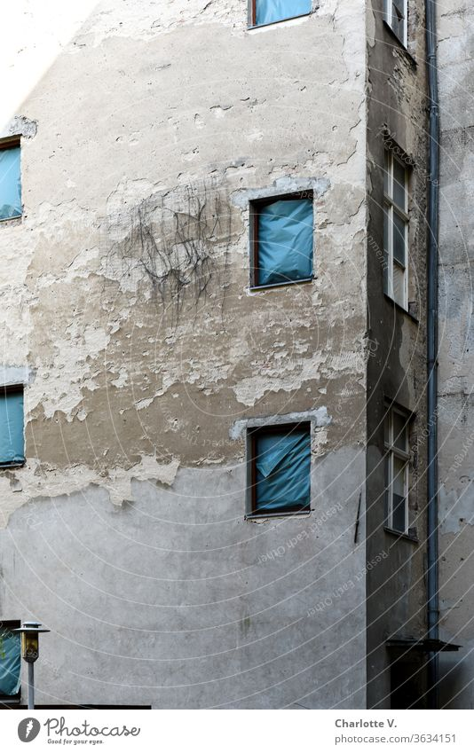 Old | house facade with flaking plaster, with blue tarpaulins instead of windows and a lamp Facade Flake off dilapidated Window hung imposed Rain gutter