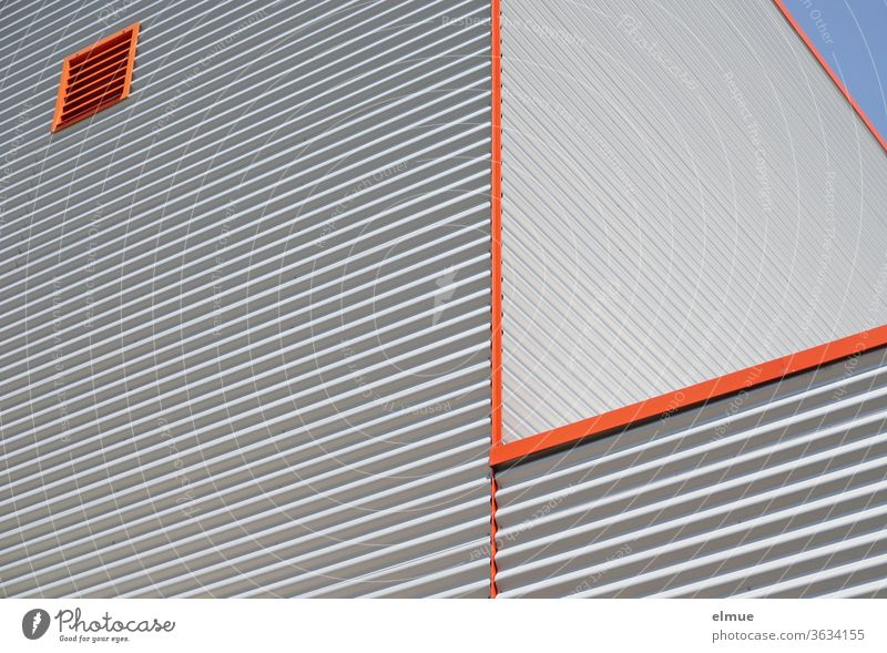 Partial view from a frog's perspective of a functional building made of grey corrugated iron, orange edges and an orange square ventilation window built
