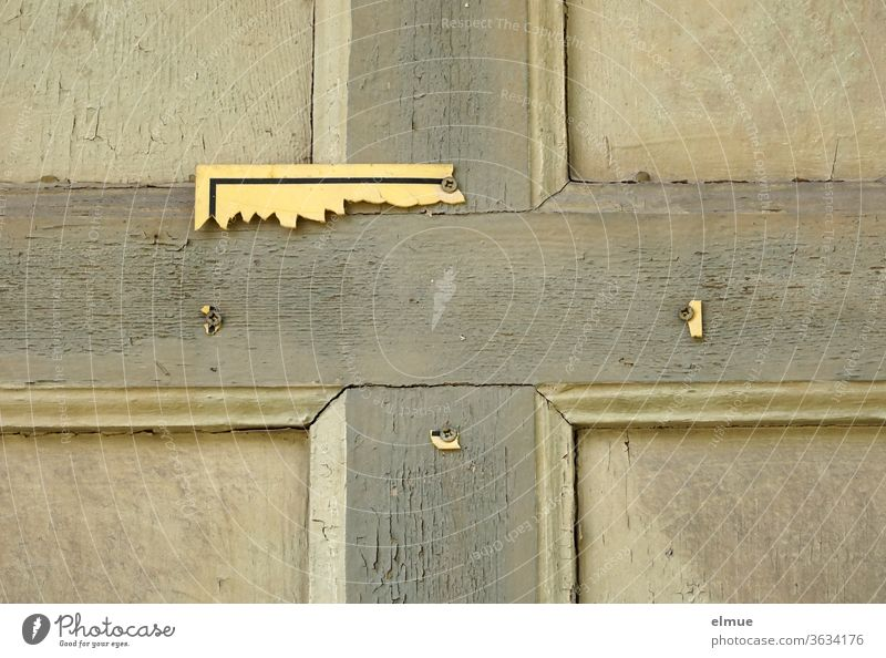 on a dilapidated wooden door you can see the remains of a yellow sign Wooden door Broken Crucifix broken Clue Illegible cross-headed screw Signage Warning sign