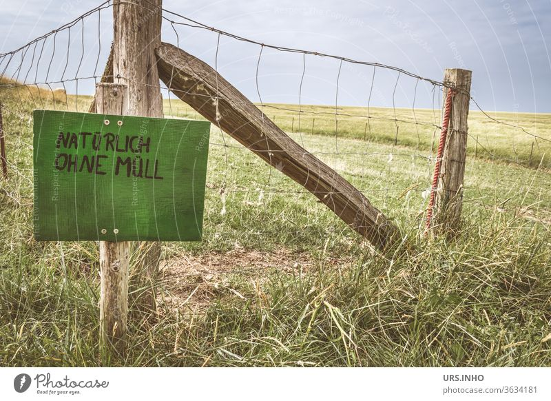 green sign with the inscription NATURALLY WITHOUT WASTE on a pasture fence Meadow Willow tree Fence Signs and labeling Signage Characters Typography leap