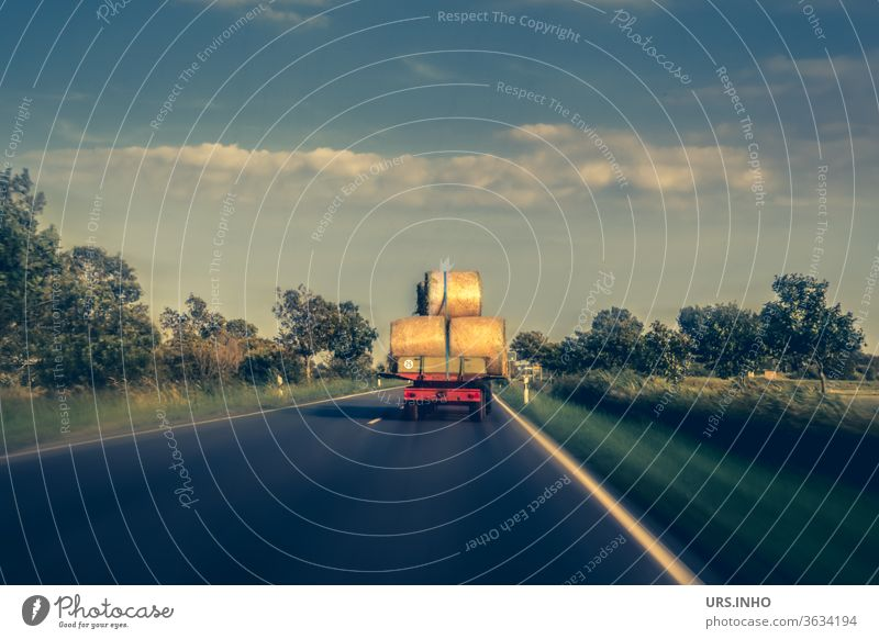 a tractor loaded with hay bales drives on a country road Tractor Hay bale Country road Agriculture Harvest Nature cloudy Summer Colour photo Field fields