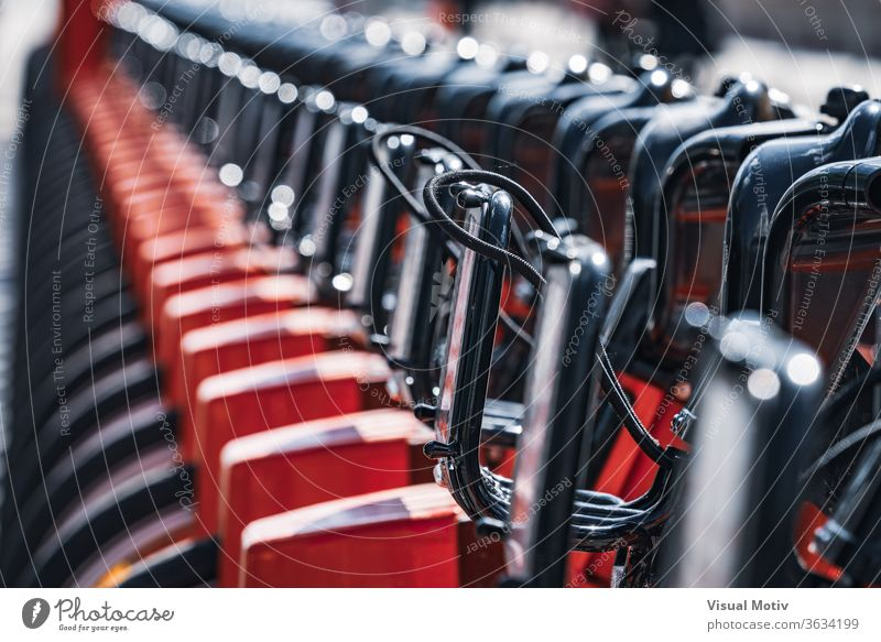 Abstract detail of a row of modern rental bicycles parked on a city street parking sunny daytime urban transport town exterior contemporary vehicle public bike