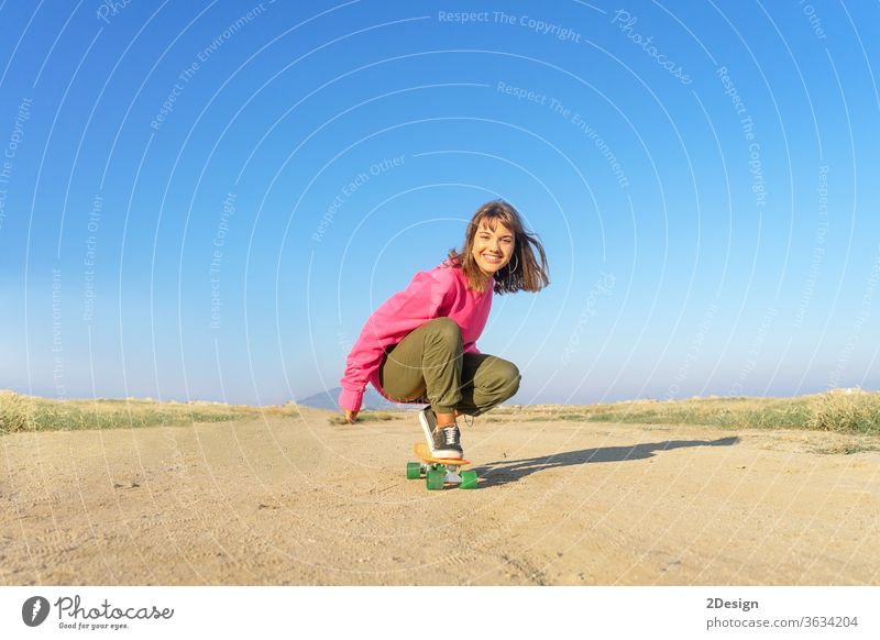 Young woman with pink jersey skateboarding in a footpath urban 1 fun young girl fashion latin hispanic copy space smile 20s speed brunette music cute active