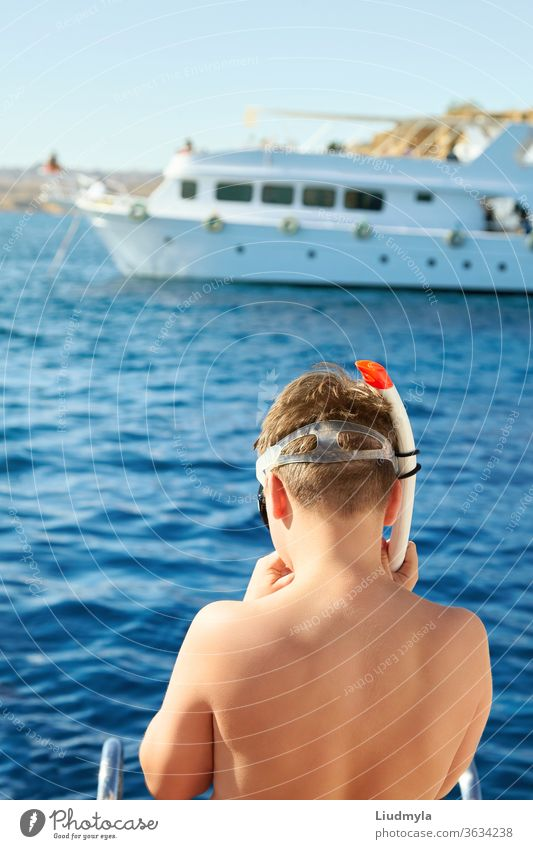 A boy is putting on a diving mask ready to swim in the sea. White yacht is on the background active beach blue child concept coral curious dive enjoyment