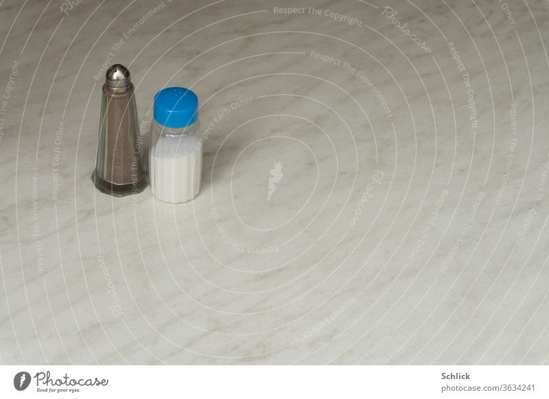 Salt and pepper stand alone on a white marble slab Pepper Salt caster Pepper caster Marble White Table Lonely a lot of free text space Plastic Glass Metal